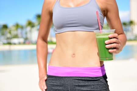 living: Fitness woman drinking green vegetable smoothie after running exercise.  Close up of smoothie and stomach. Healthy lifestyle concept with fit female model outside on beach.