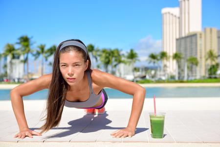 健康的なライフ スタイル フィットネス女性運動訓練腕立て伏せを行う緑の野菜スムージーを飲みます。運動を行うエクササイズ健康女性アスリート 写真素材