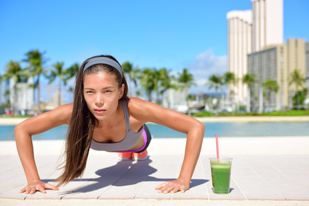 Healthy lifestyle fitness woman exercising drinking green vegetable smoothie doing push-ups training. Healthy female athlete working out doing exercise push ups on beach.  Asian Caucasian female girl.