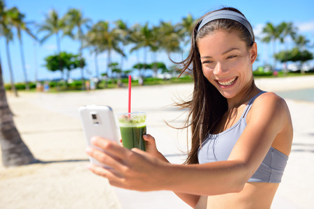 are taking: Fitness selfie woman drinking green vegetable smoothie taking self portrait photograph with smart phone after running exercise workout on beach. Healthy lifestyle with fit Asian Caucasian girl.