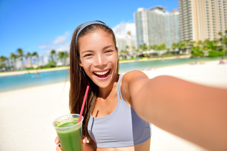are taking: Fitness girl drinking green vegetable smoothie taking self portrait photograph with smart phone after running exercise workout on beach. Healthy lifestyle with fit Asian Caucasian woman.