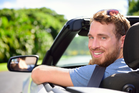 Car driver - young man wearing safety belt driving convertible on road trip in summer. Caucasian male looking at camera. photo