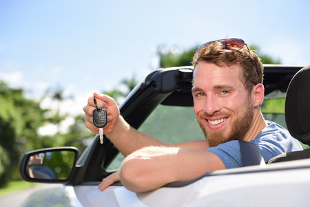 purchase: Man driving rental car showing new car keys happy. Young adult excited on road trip with key for cars leasing or rental or purchase. Stock Photo
