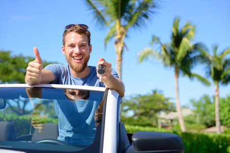 rental: Car driver showing keys and thumbs up happy. Young man holding car key for new leasing convertible. Rental cars or drivers licence concept with male driving cabriolet on road trip.