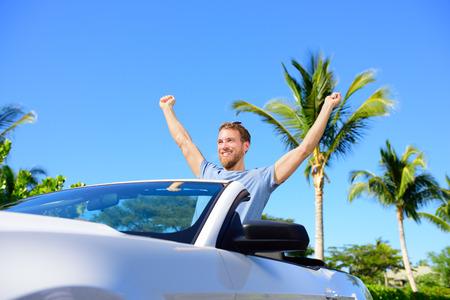 公路旅行旅行 - 驾驶汽车在自由的自由人。欢呼在敞篷车的愉快的年轻成人为他的暑假