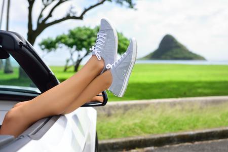 Ontspannende vakantie auto road trip reizen met de voeten het raam. Cabriolet vakantie concept met vrouwelijke benen in de voorkant van Oahu oriëntatiepunt: Hat Chinaman in Hawaii, USA.