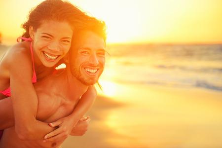 puesta de sol: La pareja de amantes en el amor que data de la diversi�n en la playa retrato. Hermosa sana adultos j�venes novia que lleva a cuestas en novio abrazando feliz. Citas multirracial o el concepto de sana relaci�n. Foto de archivo
