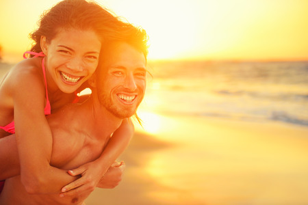 wellness: Lovers couple in love having fun dating on beach portrait. Beautiful healthy young adults girlfriend piggybacking on boyfriend hugging happy. Multiracial dating or healthy relationship concept.