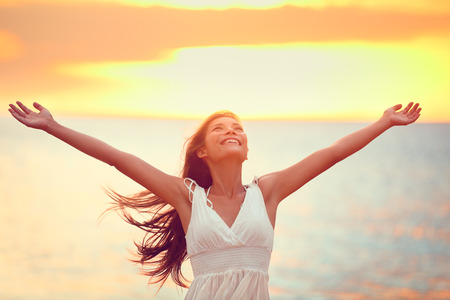 Free happy woman arms up praising freedom at beach sunset. Young adult enjoying breathing freely fresh air. Stock Photo