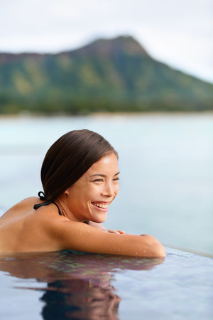 Holiday woman swimming at beach on Hawaii travel. Asian chinese young lady relaxing in infinity pool in luxury hotel resort on Waikiki beach in Honolulu, Oahu, Hawaii, USA. photo