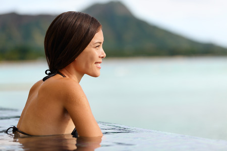 Vacation woman swimming at infinity pool on Hawaii. Beautiful asian young female adult enjoying happy holiday travel at Waikiki beach in Honolulu city, Oahu, Hawaii, USA. Summer destination holidays. photo