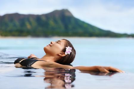 ハワイの休暇ウェルネス プール スパ女性の高級ホテル リゾートに暖かい水でリラックス。米国ハワイ州オアフ島ホノルルのワイキキ ビーチで若い 写真素材