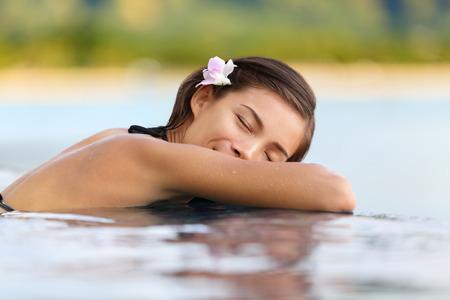 getaways: Mujer de relajaci�n en la piscina del hotel de lujo en vacaciones - viajes de vacaciones. Persona de sexo femenino asi�tica joven que duerme en balneario de la piscina en el complejo de hotel en una escapada ex�tica. Foto de archivo
