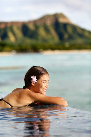 Travel vacations woman on holiday at beach resort hotel pool. Beautiful asian young adult relaxing in the sun on Waikiki, Oahu, Honolulu, Hawaii. USA vacation destination. photo