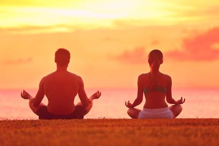 Meditatie yoga paar mediteren op serene strand zonsondergang. Meisje en man ontspannen in lotus houding in kalme zen moment in de oceaan tijdens yoga vakantie klasse op terugtocht toevlucht.