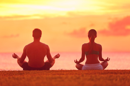 Meditation yoga couple meditating at serene beach sunset. Girl and man relaxing in lotus pose in calm zen moment in the ocean during yoga holiday class at resort retreat. Archivio Fotografico