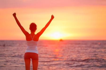아름다운 해변 일몰 행복 응원 성공을 축 하하는 여자입니다. 하늘을 향해 팔을 제기보기를 즐기는 피트니스 소녀. 야외 행복 무료 자유 스포츠 개념