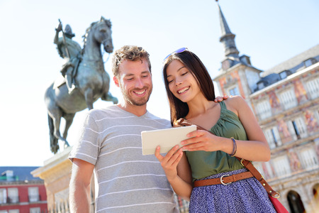 ebook: Madrid tourists using tablet travel app guidebook ebook on Plaza Mayor by statue of King Philip III. Tourist couple sightseeing visiting tourism landmarks and attractions in Spain. Young woman and man