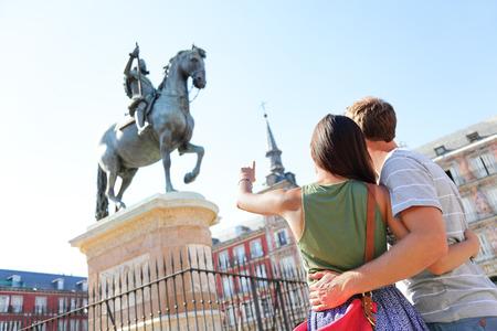 Madrid toeristen op de Plaza Mayor te kijken naar het standbeeld van koning Filips III. Reizen paar sightseeing bezoeken van toeristische bezienswaardigheden en attracties in Spanje. Jonge vrouw en man op reis. Stockfoto