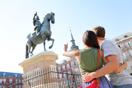 Madrid tourists on Plaza Mayor looking at statue of King Philip III. Travel couple sightseeing visiting tourism landmarks and attractions in Spain. Young woman and man travelling.