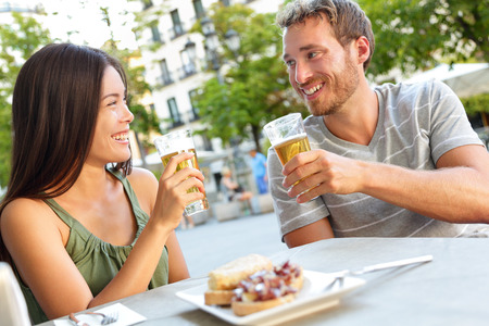 カップルはマドリード、スペインでビールを飲みながらタパスを食べるします。ロマンチックな男と女のマドリードの広場に地元の伝統的な料理を