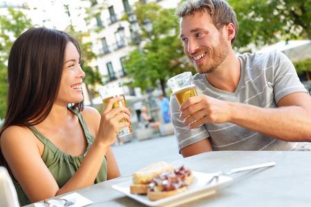 커플 스페인 마드리드에서 맥주를 마시는 타파스를 먹는. 마드리드 광장에서 지역 전통 음식을 즐기는 낭만주의 남자와 여자. 아시아 여자와 백인
