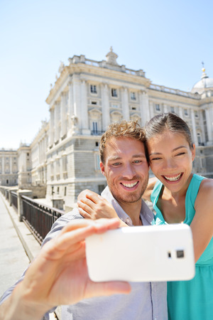tourist attractions: Couple taking selfie photo on smartphone in Madrid. Romantic man and woman in love using smart phone to take self-portrait photograph on travel in Madrid, Spain.