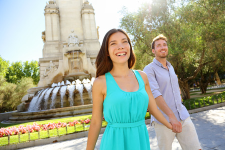 Couple walking on Plaza de Espana Madrid a popular tourist destination landmark. Romantic couple visiting Spanish tourists attractions sightseeing in Madrid, Spain. Asian woman, Caucasian man.