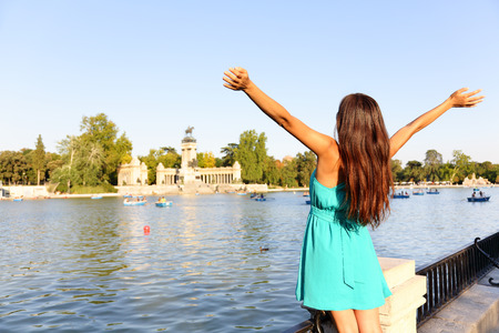 parque del buen retiro: Happy success woman in Madrid park El Retiro. Successful girl cheerful with arms up outstretched in by lake Parque el Retiro in Madrid, Spain, Europe. Woman in summer dress. Stock Photo