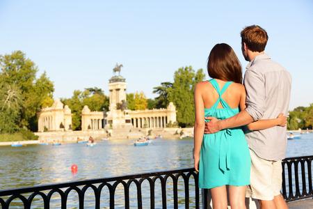 愛のエル レティーロ公園、マドリッドでのロマンティックなカップル。愛好家は、湖や記念碑の景色を楽しんでいます。しんじゅく多文化共生男と
