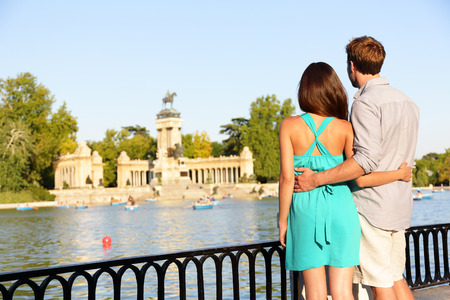 Romantic couple in love in El Retiro park, Madrid. Lovers enjoying view of lake and monument. Multicultural man and woman relaxing in el Retiro in Madrid, Spain, Europe.