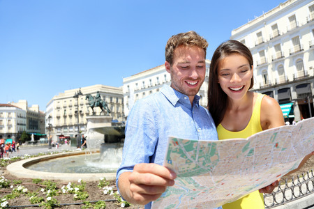 Tourists couple with map in Madrid. Sightseeing people looking at map for tourist attractions and famous landmarks while visiting Puerta del Sol in Madrid, Spain. Multiracial couple. photo