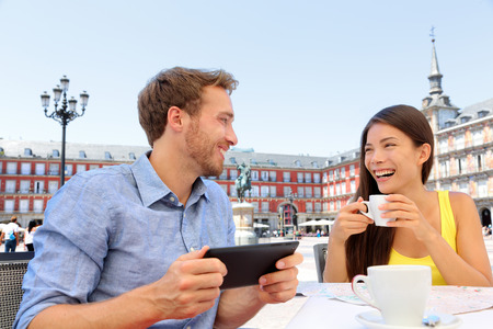 Madrid tourists at cafe drinking coffee having fun using tablet travel app on Plaza Mayor. Tourist couple sightseeing visiting tourism landmarks and attractions in Spain. Young woman and man photo