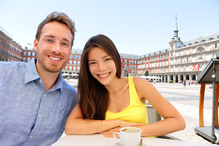 Madrid tourists taking selfie picture at cafe drinking coffee having fun on Plaza Mayor. Portrait of tourist couple sightseeing visiting tourism landmarks and attractions in Spain. Young woman and man photo