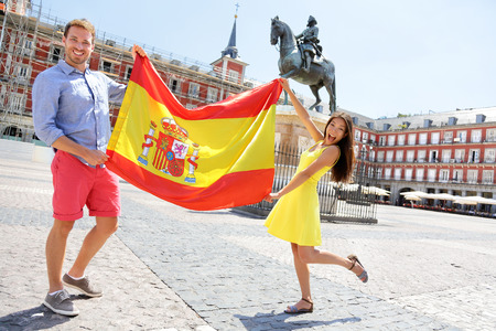 Spanish flag. People showing Spain flag in Madrid on Plaza Mayor. Happy cheering celebrating young woman and man holding and showing flags to camera on the famous square. Standard-Bild