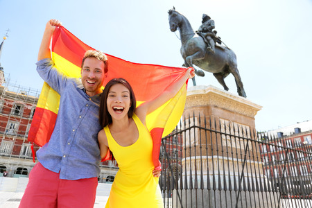 Madrid people showing Spain flag on Plaza Mayor cheerful and happy in Spain. Cheering celebrating young woman and man holding and showing flags to camera on the famous square in front of statue.