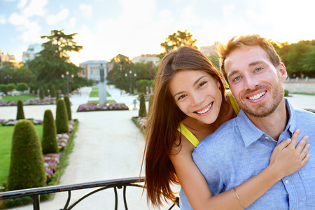 Portrait of Romantic couple embracing in love looking at camera. Multicultural man and woman smiling happy in el Retiro in Madrid, Spain, Europe. Asian girl, young Caucasian man.