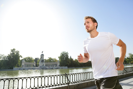 man working out: Jogging man running in city park El Retiro Madrid. Male runner exercising and training on run living healthy active lifestyle in Buen Retiro Park, Parque el Retiro in Madrid, Spain, Europe. Stock Photo