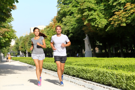 Running couple runners jogging in city park. Exercising woman and man runner training together on run living healthy active lifestyle in Buen Retiro Park, Parque el Retiro in Madrid, Spain, Europe.