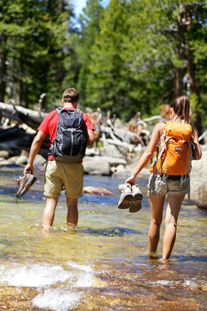 hiking: Hikers group walking barefoot crossing river in forest. Adventure people on hike hiking in nature holding shoes and boots to cross with wet feet. Stock Photo