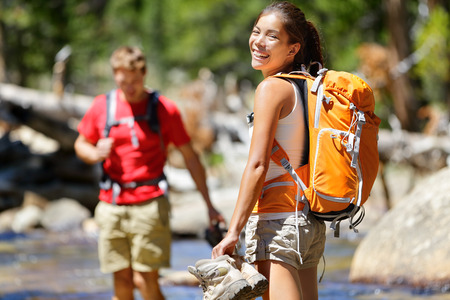 Hiking friends having fun crossing river in forest. Young happy adults barefoot walking in water with wet feet on an adventure trip hike in nature. Stock Photo