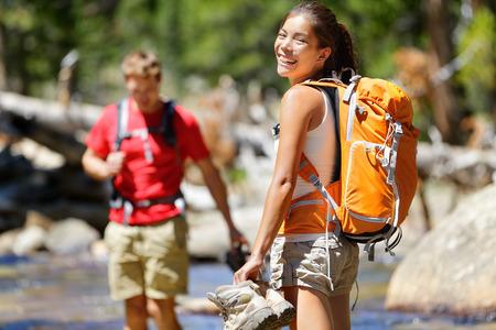Wandelen vrienden plezier oversteek rivier in het bos. Jonge gelukkige volwassenen lopen op blote voeten in het water met natte voeten op een avontuurlijke reis wandeling in de natuur.