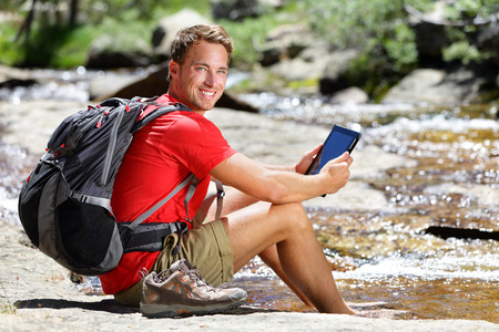 Tablet computer man hiker relaxing by river holding ebook reader reading e book or map, hiking in Yosemite, USA using travel app or map during hike. Stock Photo