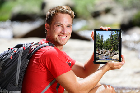Hiking man showing nature forest picture on tablet. Young adult taking pictures with digital tablet computer of landscape in Yosemite National Park, California, USA. photo