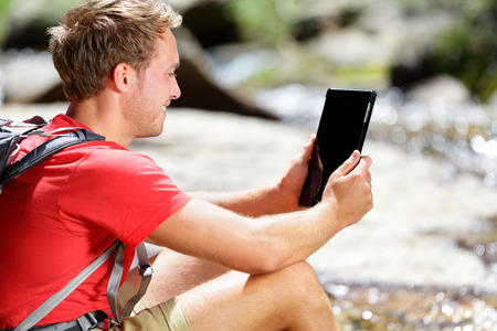 Tablet computer man hiker hiking in Yosemite, USA using travel app or map during hike, resting by river. Caucasian male hiker relaxing on a summer day. photo
