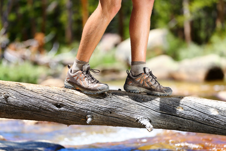 Hiking man crossing river in walking in balance on fallen tree trunk in nature landscape. Closeup of male hiker trekking shoes outdoors in forest balancing on tree. Balance challenge concept.