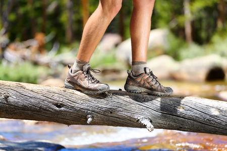 Wandelen man het oversteken van de rivier in het lopen in balans op omgevallen boomstam in de natuur landschap. Close-up van mannelijke wandelaar trekking schoenen buiten in het bos balanceren op boom. Evenwicht uitdaging concept.