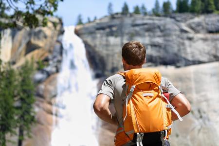 Wandelaar wandelen met rugzak naar waterval in Yosemite park in de mooie zomer natuur landschap. Portret van mannelijke volwassene terug permanent buiten. Stockfoto