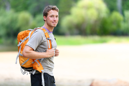 trips: Hiking man portrait with backpack walking in nature. Caucasian man smiling happy with forest in background during summer trip in Yosemite National Park, California, USA. Stock Photo