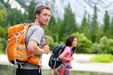 mochila viaje: Excursionistas - personas senderismo, hombre mirando monta�a naturaleza paisaje esc�nico con la mujer en el fondo. Feliz pareja joven multicultural en el Parque Nacional Yosemite, California, EE.UU.
